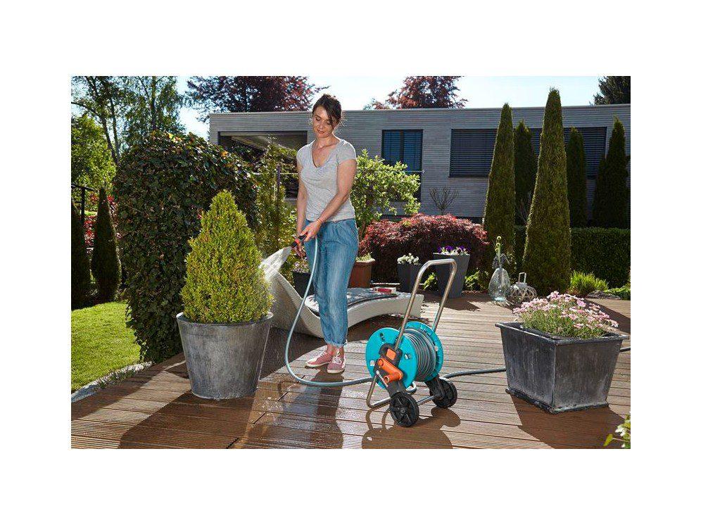 Kvinde Vander Haveplanter På Terrasse Med Turkis Slangevogn