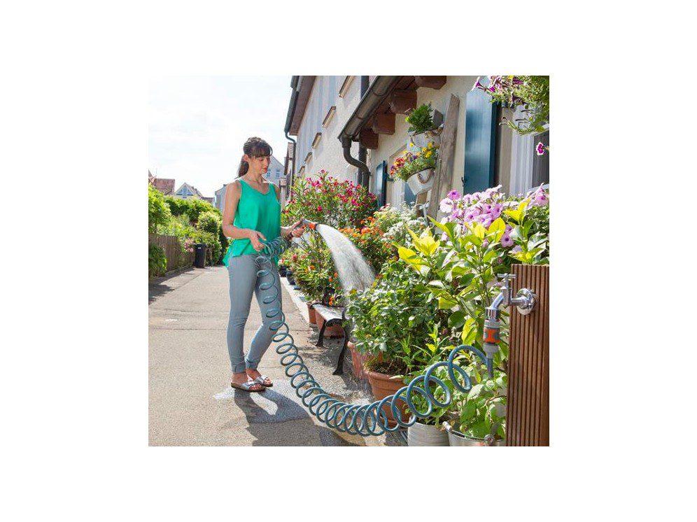 Kvinde Vander Blomster På Terrasse Med Spiralvandslange.